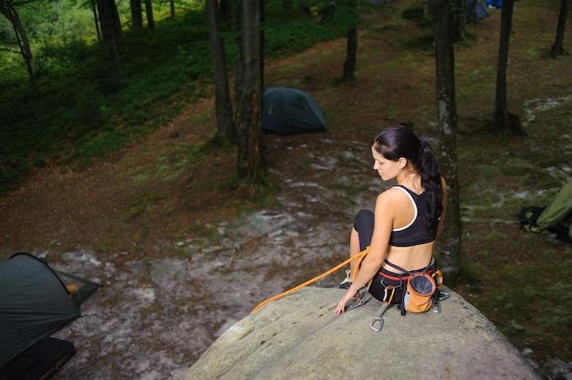 Scalatore femminile che si siede sul grande masso naturale nella foresta Foto Premium