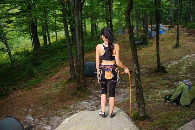Scalatore femminile che sta sul grande masso naturale nella foresta Foto Premium