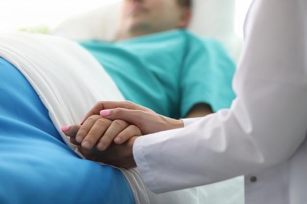 Le mani femminili di medico tengono il braccio maschio in ospedale medico Foto Premium