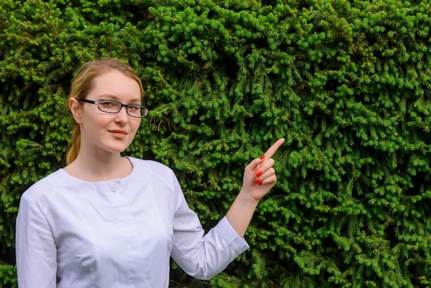 Medico femminile con il dito indica su sul fondo verde del fogliame. sviluppi scientifici nell'industria alimentare e medica Foto Premium