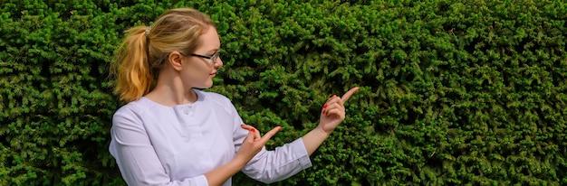 Medico femminile con le dita rivolte verso l'alto. nutrizionista in camice bianco e bicchieri con copia spazio. Foto Premium
