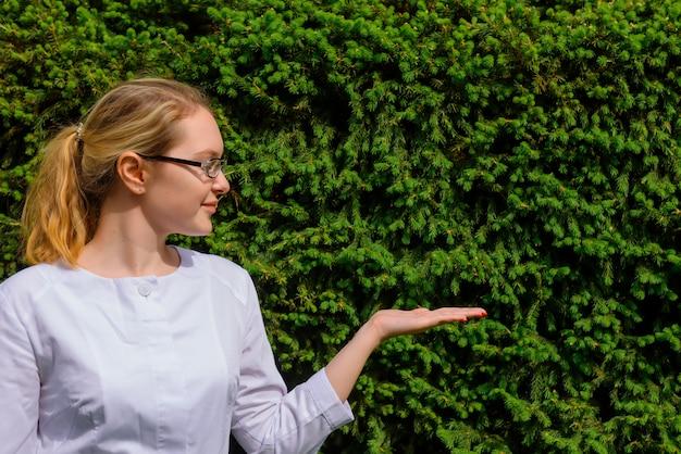 Dottoressa con palmo in su. scienziato della donna in camice e vetri su verde naturale con lo spazio della copia. immagine per la pubblicità di sviluppi scientifici nel settore alimentare e medico. Foto Premium