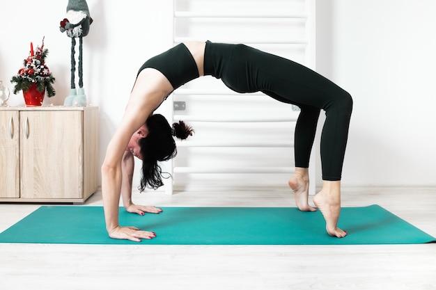 Femmina che fa yoga nella sua casa Foto Premium