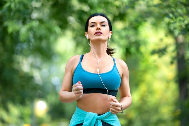 Il corridore femminile in auricolari si sta allenando nel parco Foto Premium