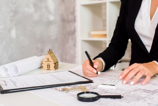 Ingegnere femminile che scrive un documento nel suo ufficio Foto Premium