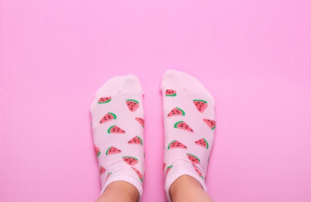 Piedi femminili in calzini colorati con stampa anguria su sfondo rosa pastello. vista dall'alto copia spazio. Foto Premium