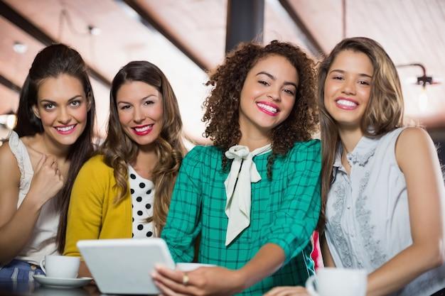 Amici di sesso femminile utilizzando la tavoletta digitale nella caffetteria Foto Premium
