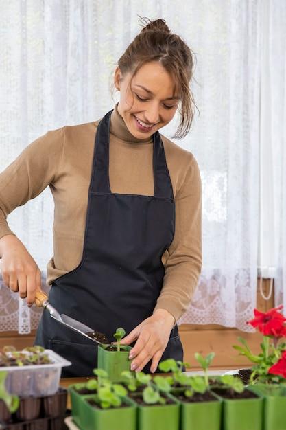 Giardiniere femminile che coltiva piante nel giardino di casa, giovane bella donna che ripianta microgreens verdure erbe piantina in vasi, coltivazione di alimenti, prodotti biologici, giardinaggio sostenibile a costo zero Foto Premium