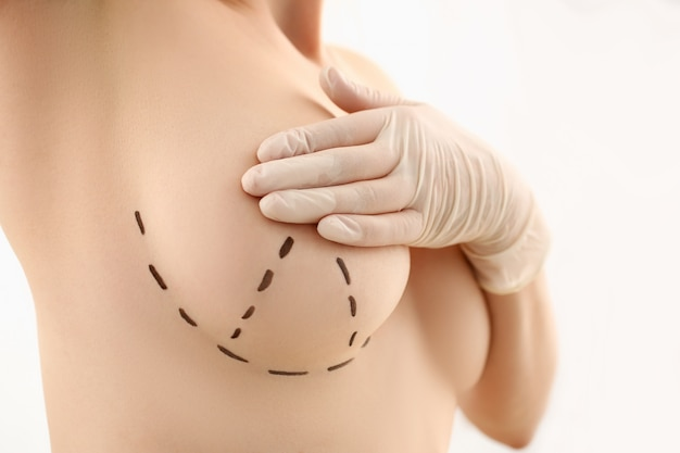 Mano femminile in guanti che tengono il primo piano del seno Foto Premium