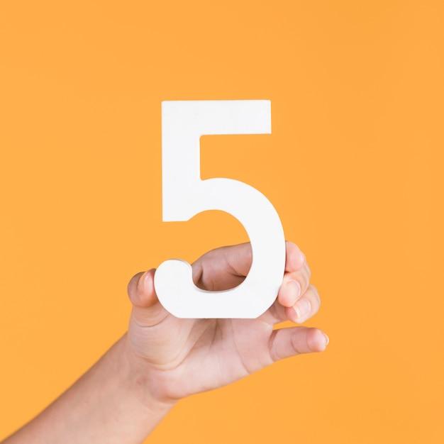 Mano femminile alzando il numero 5 su uno sfondo giallo Foto Premium