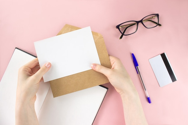 Mano femminile che tiene carta bianca. sketchbook, occhiali da vista, carta di credito laici piatta Foto Premium