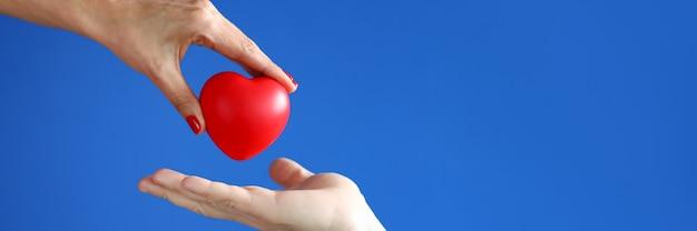 La mano femminile passa il cuore rosso alla mano maschio. gentilezza e concetto di carità Foto Premium