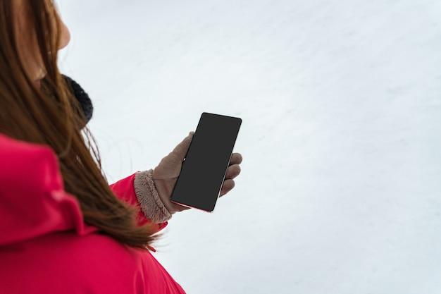 Mano femminile in guanto invernale e cappotto invernale rosso che tiene smart phone con schermo vuoto per copia spazio Foto Premium