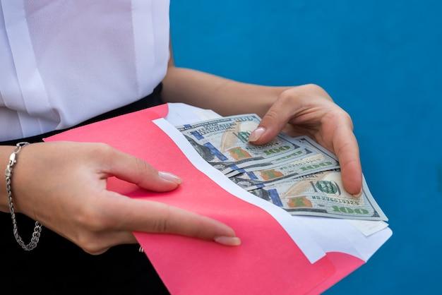 Mani femminili in manette che tengono una busta con i dollari. il concetto di corruzione e concussione Foto Premium