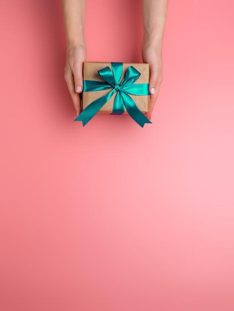 Le mani femminili tengono la confezione regalo su sfondo rosa, copia spazio verso il basso. la ragazza caucasica passa il contenitore di regalo della tenuta in carta da imballaggio del mestiere con il nastro di raso verde. Foto Premium