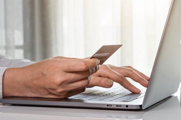 Mani femminili che tengono una carta di credito per effettuare il pagamento in linea con il computer portatile Foto Premium