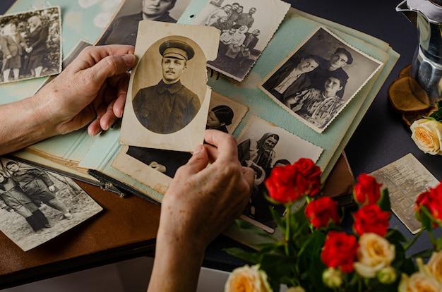 Mani femminili che tengono e vecchia foto di suo nonno. album fotografico vintage con foto. concetto di valori familiari e di vita. Foto Premium