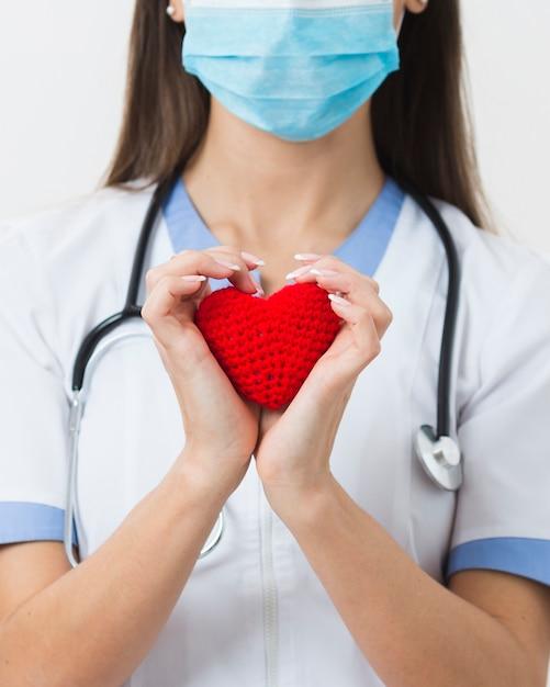 Mani femminili in possesso di un cuore di peluche Foto Premium