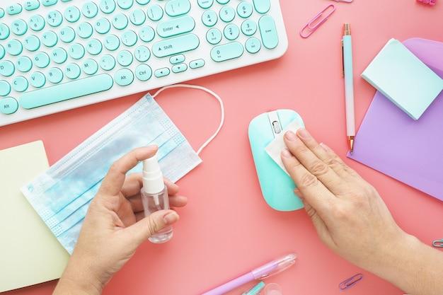 Le mani femminili puliscono il mouse con un tovagliolo e una soluzione disinfettante speciale. tastiera, lavagna per appunti, penne, mouse, adesivi, graffette e una maschera medica sul desktop. Foto Premium