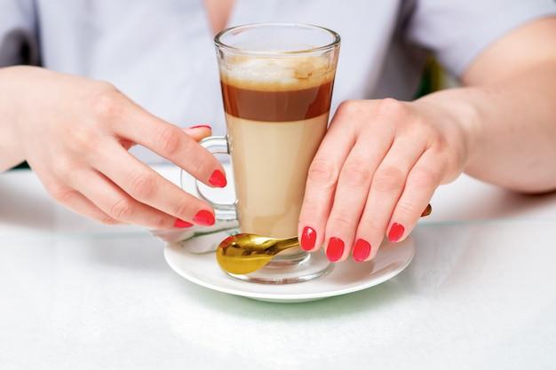 Mani femminili con perfetta manicure rossa tiene tazza di caffè cappuccino da vicino. Foto Premium