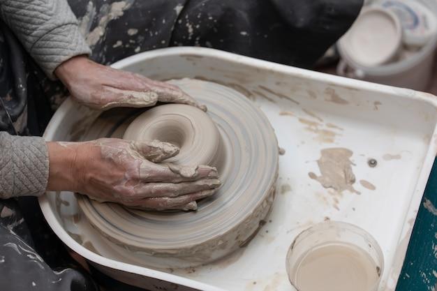 Mani femminili che lavorano sulla ruota di ceramica Foto Premium