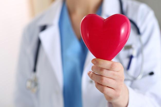 Mani di medico di medicina femminile che tengono il cuore rosso del giocattolo davanti al suo primo piano del petto. aiuto medico, assistenza cardiologica, salute, profilassi, prevenzione, assicurazione, chirurgia e concetto di rianimazione Foto Premium