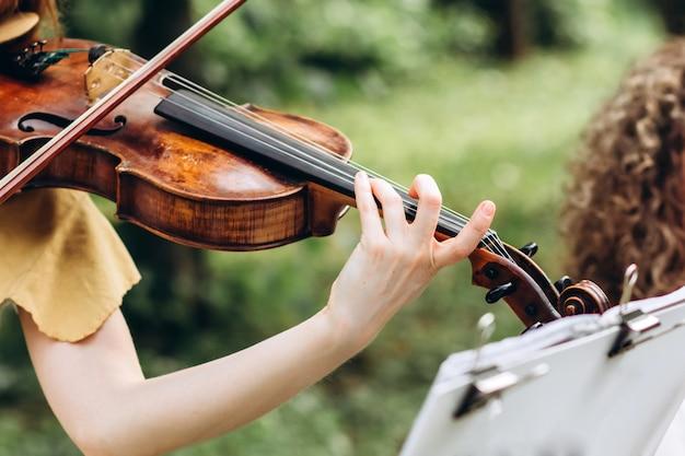 Musicista femmina si esibisce a un matrimonio all'aperto. Foto Premium