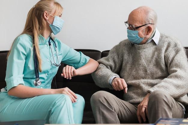 Gomito femminile dell'infermiera che tocca l'uomo anziano durante la pandemia Foto Premium