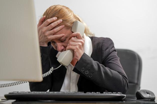 La responsabile dell'ufficio femminile è sotto stress davanti a un laptop che risponde alle chiamate dei clienti Foto Premium