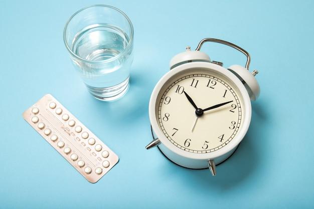 Contraccettivi orali femminili, un bicchiere d'acqua e una sveglia su un blu. Foto Premium