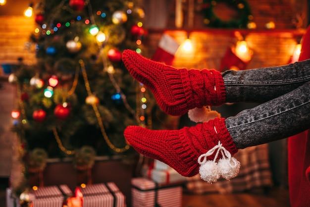 Piedi di persona di sesso femminile in calzini rossi allegri, albero di natale con decorazioni Foto Premium