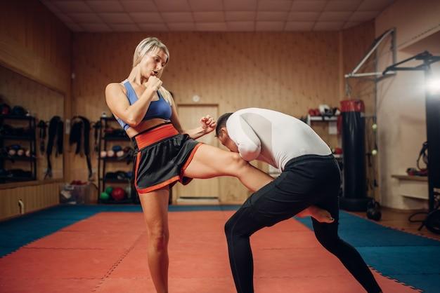 Persona di sesso femminile fa un calcio all'inguine, allenamento di autodifesa con personal trainer maschile, interno della palestra. donna in formazione, pratica di autodifesa Foto Premium