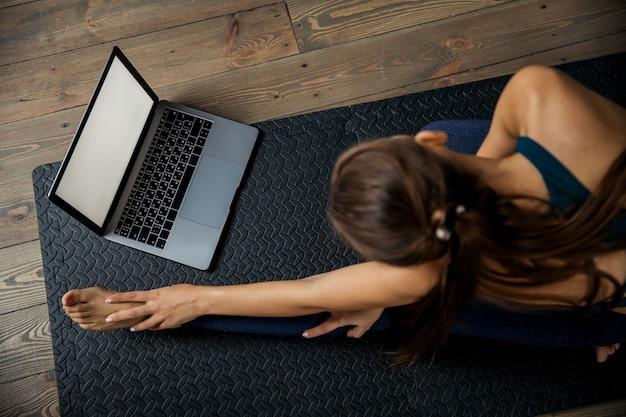 Donna che pratica yoga o pilates al chiuso sul materassino, fa esercizi e stretching, guarda video lezione online. vista dall'alto Foto Premium