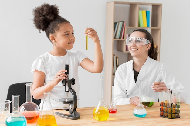 Scienziata osservando ragazza sperimentando chimica Foto Premium
