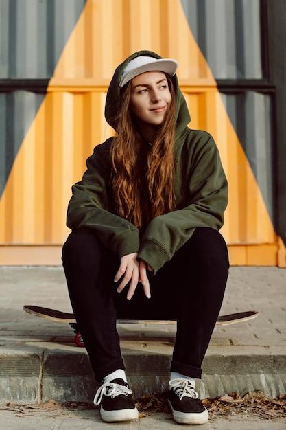 Pattinatore femminile che si siede accanto al suo skateboard all'aperto Foto Premium