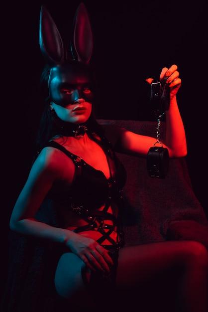Schiava in lingerie sexy con maschera bunny con manette in pelle Foto Premium