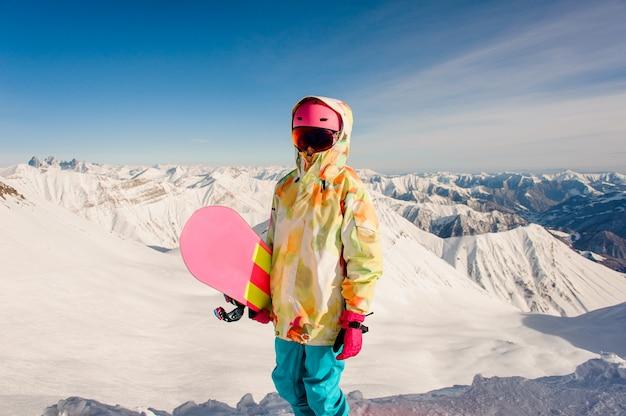 Snowboarder femminile in abiti sportivi luminosi che stanno sulla cima della montagna in georgia, gudauri Foto Premium