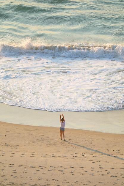 Femmina che allunga sulla spiaggia sabbiosa nella luce del sole di mattina, spiaggia di copacabana, brasile Foto Premium
