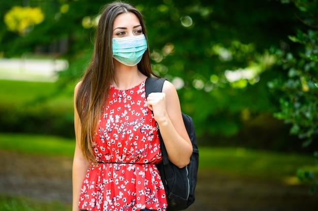 Studentessa che cammina all'aperto nel parco e indossa una maschera per proteggersi dal coronavirus Foto Premium
