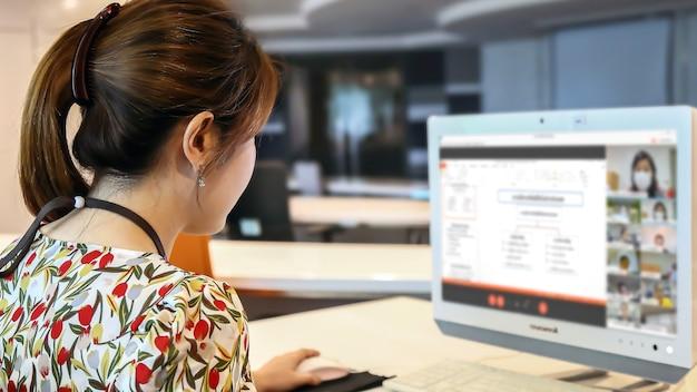 Insegnante femminile che utilizza il computer per insegnare agli studenti in linea con il programma della conferenza Foto Premium