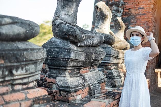 Turista femminile che indossa la mascherina chirurgica che visita il tempio di wat chaiwatthanaram Foto Premium