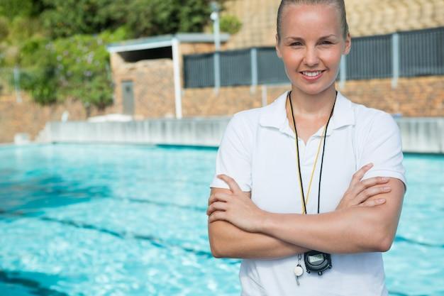 Allenatore femminile in piedi con le braccia incrociate a bordo piscina Foto Premium