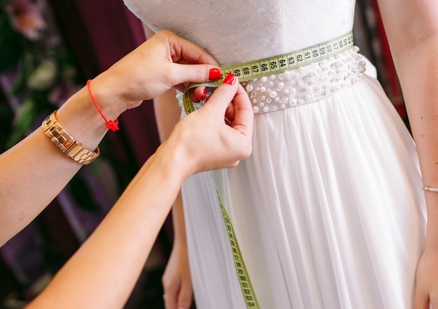 Prova femminile sul vestito da sposa in un negozio con l'assistente delle donne. Foto Premium