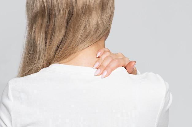 Donna in top bianco con dolore al collo e alla schiena. Foto Premium