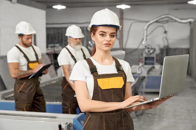Lavoratrice della fabbrica che posa con il taccuino. Foto Premium