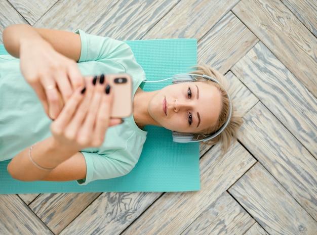 Femmina che lavora sulla stuoia e utilizzando il telefono Foto Premium