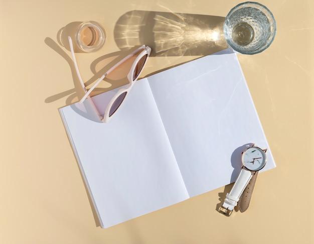 Mockup di note di blogger femminile. accessori da donna vista dall'alto, bicchiere con acqua e blocco note vuoto aperto. foglio di carta bianco con spazio per il testo Foto Premium
