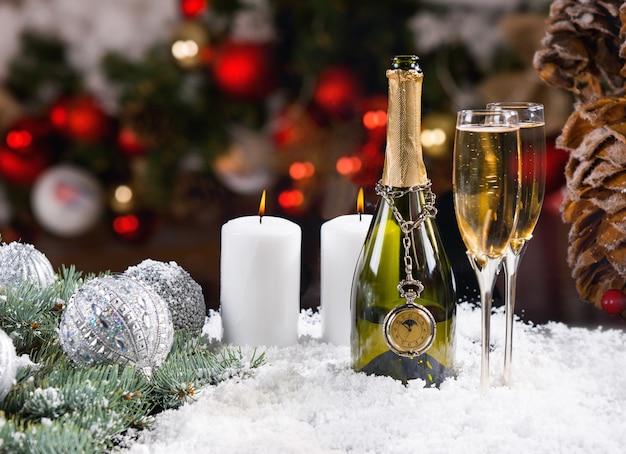 Champagne festivo e candele sulla superficie innevata Foto Premium