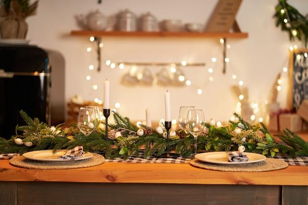 La tavola natalizia festiva è decorata con rami di un albero di natale, candele e ghirlande Foto Premium