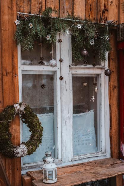 Decorazione festiva della finestra del nuovo anno con rami di abete, ghirlande e coni. segno di buon natale e bagattelle sul davanzale della finestra Foto Premium
